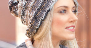 Теплая шапка с помпоном смещающейся резинкой круговыми рядами из меланжевой пряжи