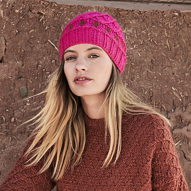 Розовая шапка с полоской жаккардовых ромбов и рельефным узором